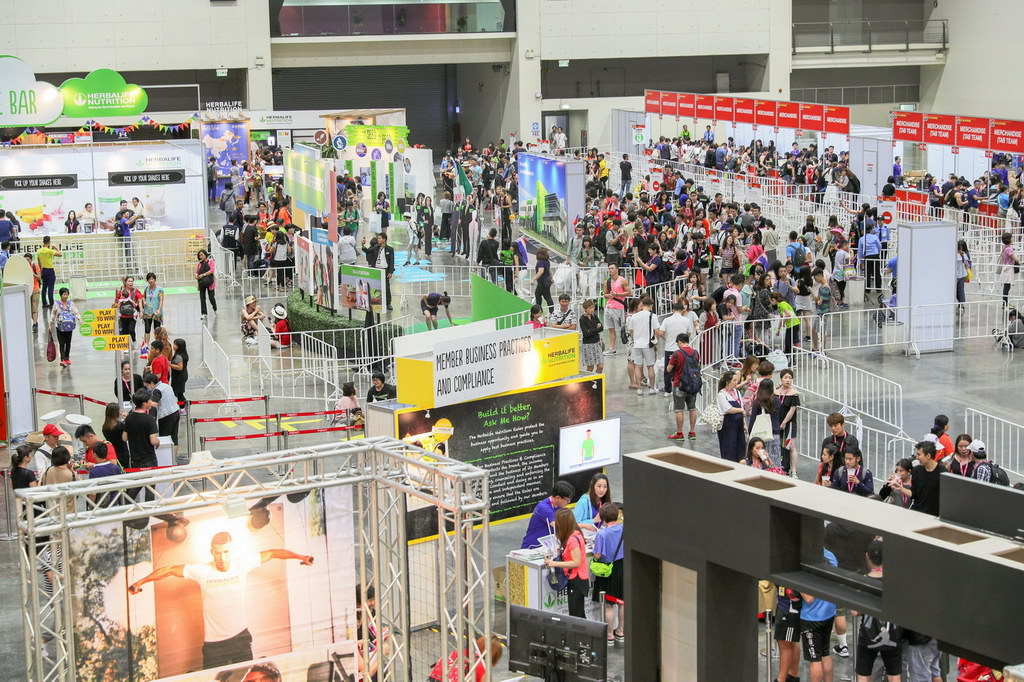 trade show in bangkok with multiple booths and people attending.