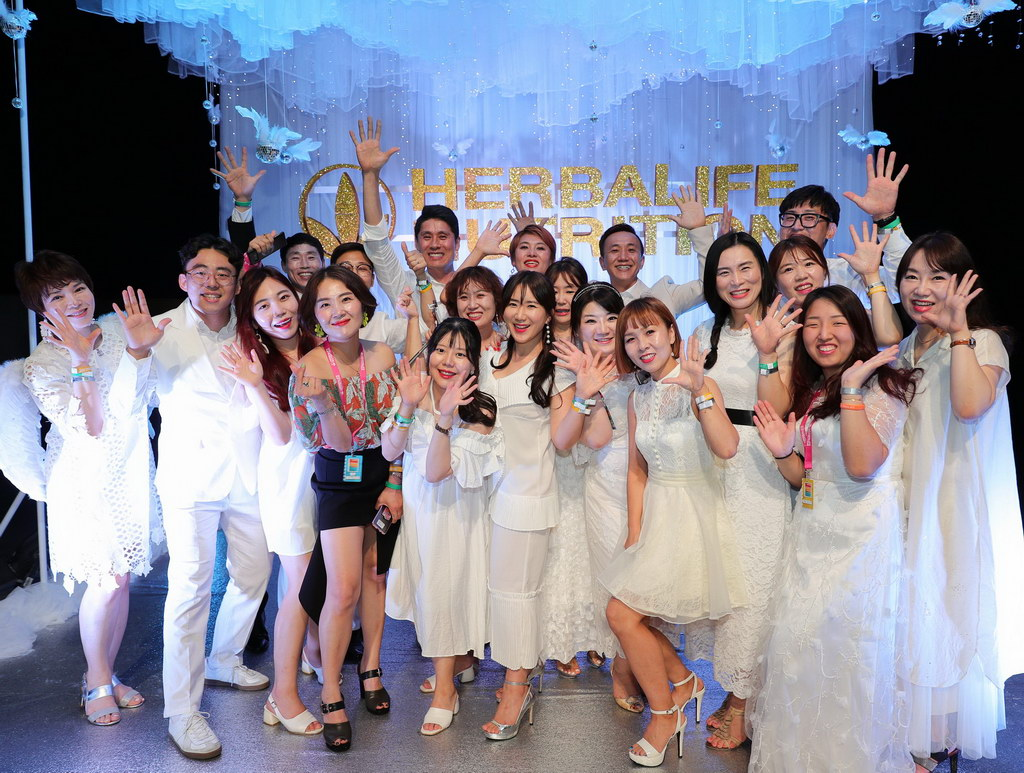 Asian party goers in white dress at an event in Thailand.