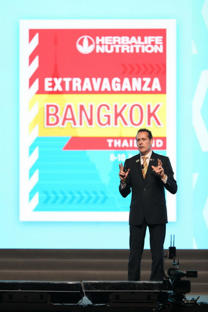 speaker on stage at a convention in bangkok.